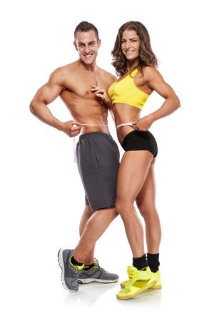 mooie jonge sportieve paar met een meetlint geïsoleerd over witte achtergrond