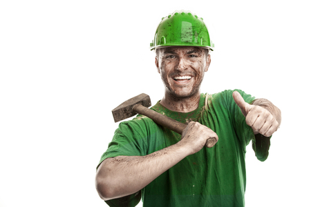 mire: Young dirty smiling Worker Man With Hard Hat helmet  holding a hammer isolated on White Background