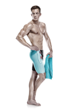 Young attractive caucasian man swimmer with goggles and towel isolated over white background photo