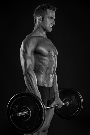 man legs: Muscular bodybuilder guy doing exercises with big dumbbell over black background
