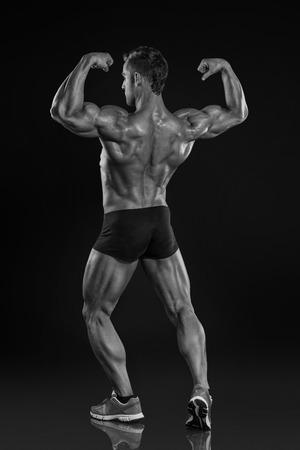 latissimus: Forte Uomo Atletico fitness Modello in posa muscoli dorsali, tricipiti, dorsali su sfondo nero