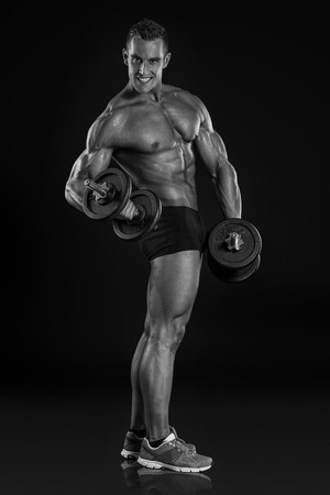 retouched: Muscular bodybuilder guy doing exercises with dumbbells over black background