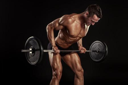 Gespierde bodybuilder man doet oefeningen met grote halter over zwarte achtergrond