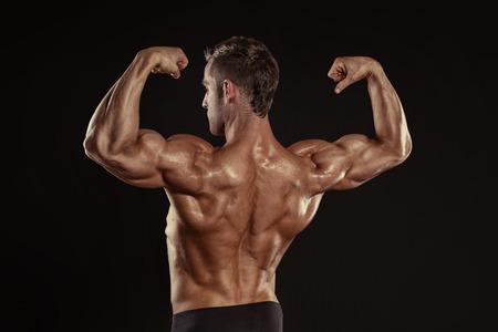 latissimus: Forte Uomo Atletico Fitness Modello in posa muscoli dorsali, tricipiti, dorsali su sfondo nero Archivio Fotografico