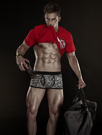 six packs: Strong Athletic Man Fitness Model Torso showing six pack abs. isolated on black background