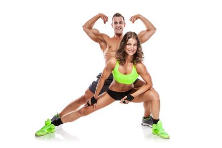 美しい若いスポーティなカップルのポーズと白い背景で隔離の筋肉を示す