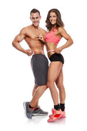 beautiful young sporty couple with a measuring tape isolated over white background photo