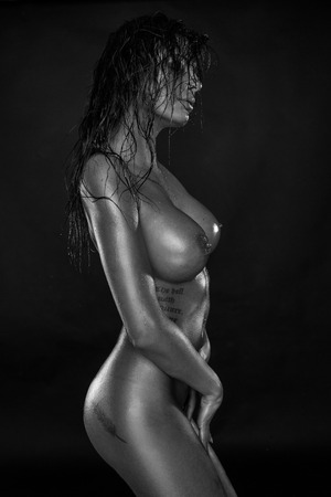 nude wet: very beautiful nude or naked woman with brown hair and super wet body isolated on black background with tattoo Stock Photo