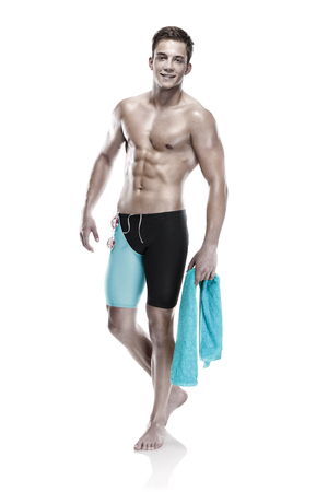 swimming shorts: Young attractive caucasian man swimmer with goggles and towel isolated over white background