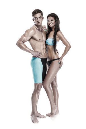 swimming shorts: Young attractive caucasian couple swimmers in swimsuits isolated over white background Stock Photo