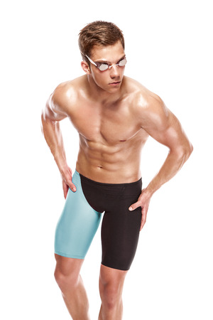 swimmers: Young attractive caucasian man swimmer with goggles and towel isolated over white background