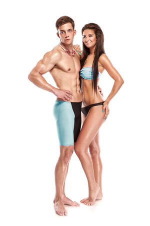 fit couple: Young attractive caucasian man swimmer with goggles and towel isolated over white background
