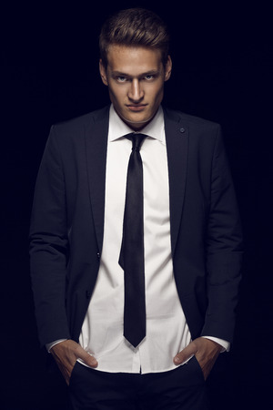Cool businessman standing on dark background (colored, retouched)