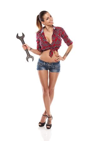 Schöne reizvolle Frau, Mechaniker holding Schraubenschlüssel auf weißem Hintergrund isoliert
