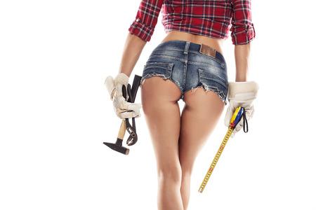 Mooie sexy vrouw monteur tonen bum bil en houden hamer tang en meetlint geïsoleerd op een witte achtergrond