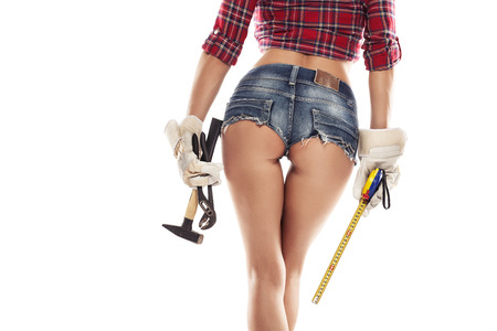 Nice sexy woman mechanic showing  bum buttock  and holding hammer pliers and measuring tape isolated over white background Standard-Bild