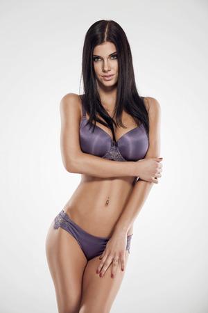 beaux seins: studio photo de poser femme sexy avec une belle lingerie sur fond blanc Banque d'images