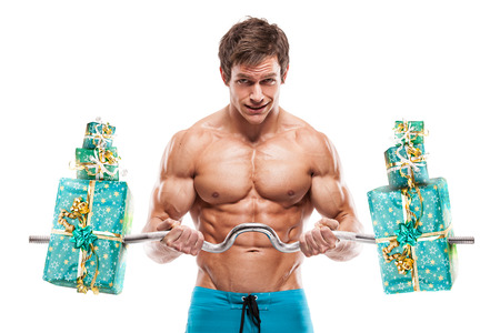 sexy birthday: Muscular bodybuilder guy doing exercises with gifts isolated over white background