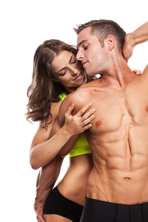 sexy nackte frau: sexy Paar, muskul�ser Mann, der eine sch�ne Frau auf einem wei�en Hintergrund