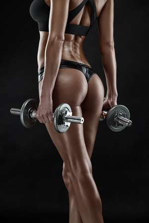 Nice sexy woman doing workout with dumbbell isolated over black background Standard-Bild