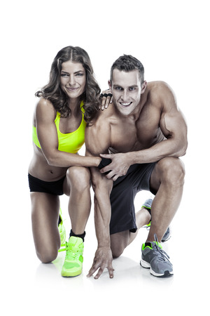 beautiful young sporty couple posing and showing muscle isolated over white background