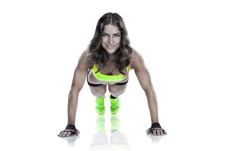 abdomen fitness: Fitness hermosa mujer haciendo flexiones de brazos j�venes aislados sobre fondo blanco