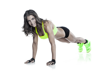 beautiful fitness young woman doing pushups isolated over white background 版權商用圖片