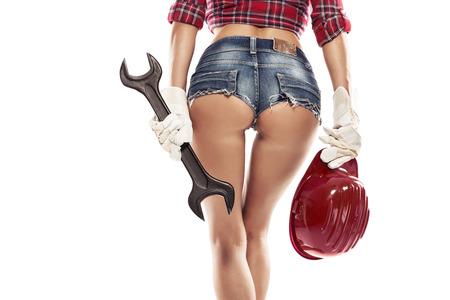 Mooie sexy vrouw monteur tonen bum bil en houden moersleutel geïsoleerd over witte achtergrond Stockfoto