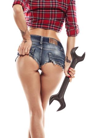 werkzeug: Sch�ne reizvolle Frau, Mechaniker zeigen bum Ges�� und h�lt Schraubenschl�ssel auf wei�em Hintergrund isoliert