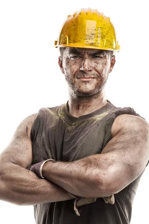 ouvrier: portrait du travailleur sale avec casque bras croisés isolé sur fond blanc Banque d'images