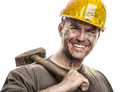 흰색 배경에 고립 된 망치를 들고 하드 모자 헬멧을 가진 젊은 더러운 작업자 남자 스톡 콘텐츠