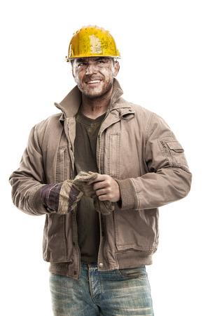 若年汚れた作業用手袋を保持している労働者男とハード帽子ヘルメットと白い背景で隔離笑みを浮かべて 写真素材