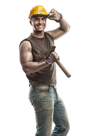 Jonge vuile Arbeider Mens Met Bouwvakker helm met een hamer en lachend op een witte achtergrond Stockfoto