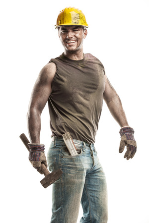 hard worker: Young dirty Worker Man With Hard Hat helmet  holding a hammer and smiling isolated on White Background