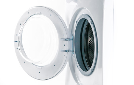 Washing machine with an open door detail on white background photo