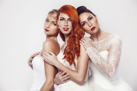 blonde females: portrait of a three beautiful woman in wedding dress isolated over white background