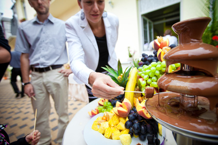 Chocolate fondue with fruits, on table, people on background