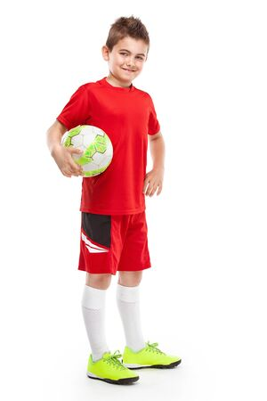 retouched: standing young soccer player holding football isolated over white background