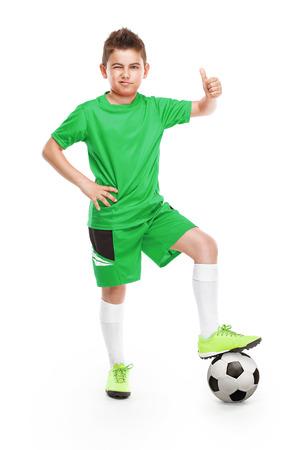 ropa deportiva: de pie joven jugador de fútbol con el fútbol aislados sobre fondo blanco