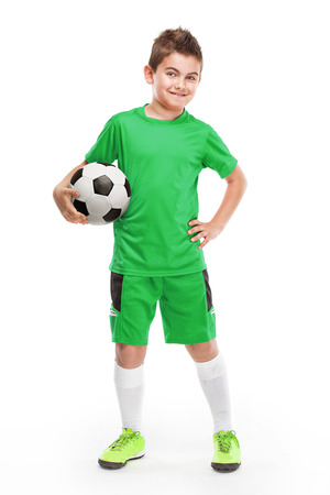 standing young soccer player holding football isolated over white background