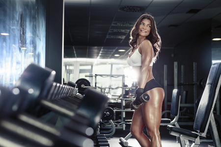 beautiful nude woman: Nice sexy woman doing workout with dumbbells  in gym