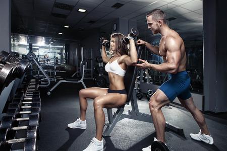 健身: 在健身房年輕漂亮的運動型的性感夫婦的鍛煉