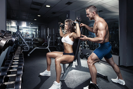 fit man: beautiful young sporty sexy couple workout in gym