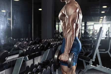 fit body: Muscular bodybuilder guy doing exercises with big dumbbell in gym Stock Photo