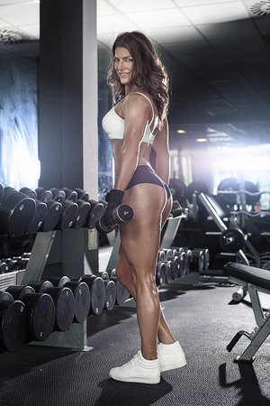 sensual nude: Nice sexy woman doing workout with dumbbells  in gym
