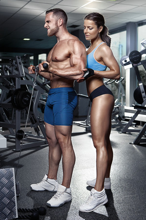 fitness hombres: hermosa joven deportiva atractiva pareja haciendo bíceps entrenamiento en gimnasia
