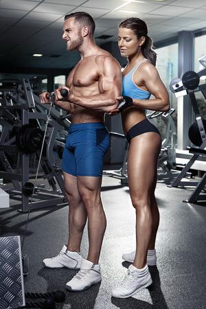 abdomen fitness: hermosa joven deportiva atractiva pareja haciendo b�ceps entrenamiento en gimnasia