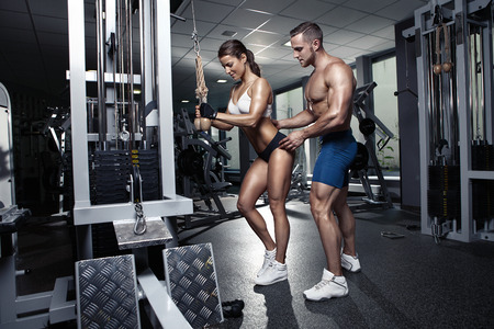 sexy abs: beautiful young sporty sexy couple doing triceps workout in gym