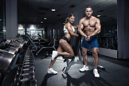 muscle girl: beautiful young sporty sexy couple showing muscle in gym
