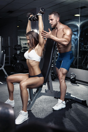 fit: beautiful young sporty sexy couple workout in gym